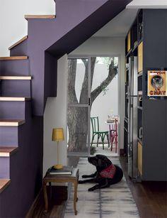 1-Pintada na cor Berinjela* (Suvinil), a escada emoldura a passagem entre a sala e a cozinha, de 7,50 m². A estante (Marcenaria Espaço Interno) tem laminado grafite e portas laqueadas de amarelo. Passadeira da Phenicia Concept.
