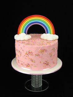 A fondant rainbow and clouds on top of a white chocolate and raspberry cake filled and covered in pink ganache with a sprinkle of sprinkles.