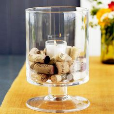 Corks and Candles Centerpiece - Play the rustic, uneven colors and natural textures of wine corks against the smooth shimmer of clear glass for a simple and elegant fall centerpiece. A large footed glass candleholder lifts the scene above the table setting, while a white votive shimmers in the center of the medley of corks.