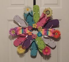 """Flip Flop Bright Daisy Sun Fun, Decorate your door or room with the summer footwear we love to wear.   This wreath is fastened with greening pins making it sturdy and heat resistant. The wreath measures approximately 22"""" across, includes 12 flip flops and comes with a variety of flower embellishment's and rhinestones. Please avoid displaying this wreath in between a storm and house door. Too much direct sunlight causes extreme heat built up."""