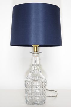 A pair of Victorian glass decanter lamps with Navy silk shades. Stylish and easy to DIY with a bottle lamp adapter kit.