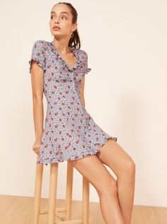 Sassy. This is a mini length, fit and flare dress with a ruffle edged v neckline, ruffled hem and ruffled sleeves.