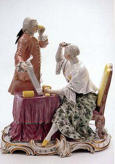 Allegorie auf die Sinne: Das Gesicht  An einem Frisiertisch sitzt eine junge Frau mit Frisierumhang und steckt sich Blütenzweige ins Haar. Ihr gegenüber steht ein Kavalier und hält ihr mit der einen Hand den Spiegel, in der anderen Hand hält er ein Fernglas.  Frankenthal, um 1760 Modell von Johann Friedrich Lück