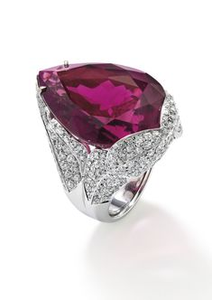 A rubellite tourmaline and diamond ring, by Margherita Burgener  Set with a pear-shaped rubellite tourmaline, weighing approximately 46.00 carats, within pavé-set diamond floral shoulders and bezel, length 3.3 cm, ring size L ½, signed 'Margherita Burgener'.