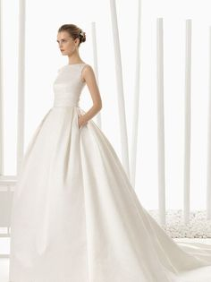 You don't want lace, sequins, or ribbons. You like crisp lines, artistic cuts and quality fabrics. That is what this Rosa Clara dress gives you. It's a bateau neckline wedding dress that you can imagine Grace Kelly wearing for her royal nuptials.
