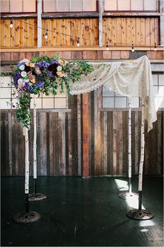Birch bark chuppah decorated with vintage French lace and a one-sided floral arrangement made up of dahlias, roses, hydrangea and clematis.