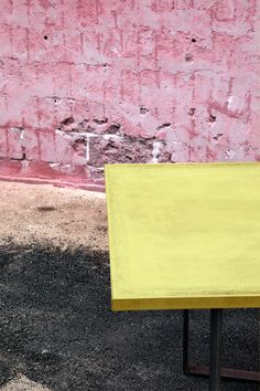 Yellow concrete table top on iron table base. Design by Storm&Müller
