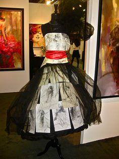 this dress form  is dressed for a runway show, covered in fashion illustrations