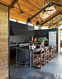 Lake|Flato designed the kitchen's cabinetry, steel hood, and island; the range and refrigerator are by Viking, and the stools are by BDDW | archdigest.com