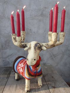 This stag is made of fireclay, it has been colored with metal oxides and fired at 1050 °C in an electric kiln. There are felt stickers on its soles. It wears a hand knitted striped wool sweater with bow detail in front. Because the wax could drip when the flames flicker, its safer to