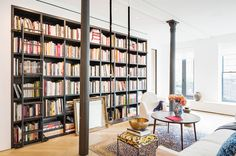 A built-in black bookshelf with floor to ceiling shelves, small round table and foot stool // library