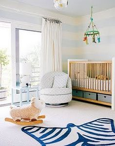 This blue nursery is surprisingly gender-neutral. Modern furnishings are softened with familiar-feeling characters and transitional patterns to create a comfortable, pretty look.