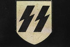 """The sig rune (or Siegrune) symbolised victory (sieg) or the sun. Adapted into the emblem of the SS in 1933 by Walter Heck, an SS Sturmhauptführer/graphic designer for Ferdinand Hoffstatter, a producer of emblems and insignia in Bonn. It consisted of two sig runes drawn side by side like lightning bolts, and was soon adopted by all branches of the SS .The device had a double meaning; as well as standing for the initials of the SS, it could be read as a rallying cry of """"Victory, Victory!"""". The…"""