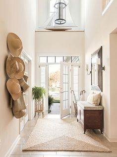 The light-suffused entry at Matthew Caughy's beach house sets off the home's welcoming, at-ease vibe with soaring ceilings, a natural-fiber rug, and an antique bench, found at a local shop, that holds board games often brought out for little ones in the family. The sconces are by Visual Comfort.