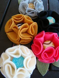 Felt flowers.  7 circle pieces.  Glue six circles into folded S's onto the seventh.  Finish with button.  Glue pin or hair clip on back.