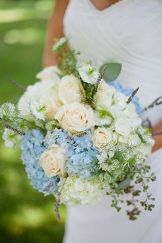 The bridal bouquet will be a clutch bouquet of light blue hydrangeas, white roses, Queen Ann's lace, fresh lavender, and small hints of seasonal greenery wrapped in ivory satin ribbon with white pearl pins and the stems showing.