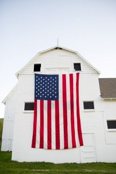 Red, white, blue flag on old white barn.