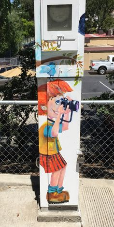 Little photographer mural on the side of a meter box in Auburn on High Street.