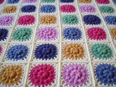 The textured circles in this crochet blanket look just like jelly moulds. They are made with raised puff stitches, giving a colourful and interesting baby blanket. The finished blanket measure 100 x 74 cm, including a simple striped border. Afghan Crochet Patterns, Crochet Squares, Crochet Motif, Crochet Stitches, Crochet Afghans, Granny Squares, Crochet Flowers, Baby Blanket Crochet, Crochet Baby