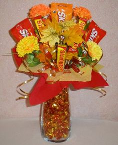 Vase, candies, silk flowers/maple leaves, floral foam/tape, red and yellow crepe paper or cellophane, gold/red/yellow curling ribbon, wooden skewers, hot glue gun, scissors, wire cutters...  Such a cute and interesting bouquet to give