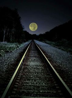 Moon over train tracks heading into the light