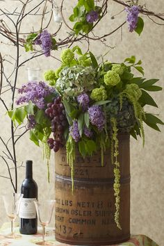 A stunning arrangement of grapes, hydrangea, lilacs, and viburnum for a wine-tasting party.