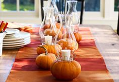 Fall tablescapes This is such a clever idea to create pumpkin lanterns with votive candles and hurricane shades. The shades can often be found at thrift stores, so this could be made inexpensively.