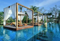 Unique swimming pool with drape shaded island pavilions located at the luxury Khao Lak Resort Hotel in Thailand.
