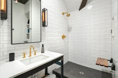 Black and white bathroom features walls clad in white stacked tiles, which continue to the open ...