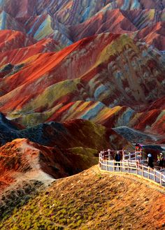 y<3 Zhangye Danxia Landform, Gansu Province, China. This naturally-formed landscape - a World Heritage site and a tourist attraction - astonishes visitors with the burst of colors with streaks of yellow, orange and red to emerald, green and blue that make it hard to believe it's real. The formation-process of this geo-park took over 24 million years in the Cretaceous age. If you plan on visiting, hope for the rain, as the vibrant hills glow even brighter after the rainfall