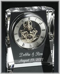 This eye-catching crystal clock allows you to see the skeleton clock movement as time passes by. The brushed silver clock face is detailed with roman numerals, a visible silver clock movement and black hands. The clock is presented in a piano finish box with a brass closure and blue velour lining. We engrave on the body of the clock for a thoughtful personalized gift to celebrate a wedding or anniversary.  $95.00