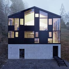 NEW FACADE WRAPS OLD HOUSE l Jochen Specht envelops a 1960s house in rural Austria by encasing its stone walls behind a new facade made up of dark timber, concrete and plenty of windows with views of the Rhine Delta and Lake Constance.