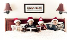 Christmas card, reading holiday books in bed with Santa hats.