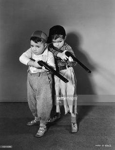 American child actors George 'Spanky' McFarland (1928 - 1993, left) and Scotty Beckett (1929 - 1968), of the Hal Roach 'Our Gang' and 'Little Rascals' comedy films, take aim with toy shotguns, circa 1935.