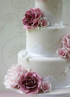Bolo de casamento decorado com rendas e flores de açúcar.