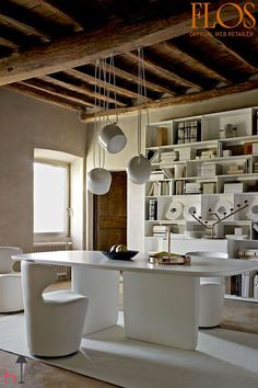 AIM lighting brings this modern interior together, matching the white table and chairs, white carpeting and wood beamed ceiling.