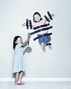 Big sister sticks little sister to the wall, but not without a grin. (Jason Lee/JWLPhotography)