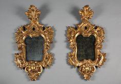 Paire de miroirs dans le style vénitien du XVIIIème siècle, en bois sculpté ajouré et doré à décor de coquilles, volutes et rinceaux.Le style rocaille succède au Baroque italien...