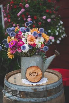 Barn wedding reception flowers. Wood round cut. Couple's initials branded on wood. Wine barrels. Doilies. Dahlias. Barn wedding. Rustic wedding.
