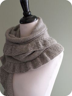 scarf knit lengthwise, then pick up stitches and a ruffle added around the outside.  free pattern.  cute!