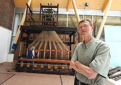 A photograph of a man standing next to an old loom