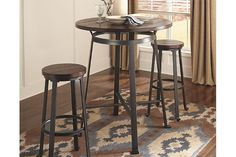 Rustic in feel with modern appeal, the Challiman dining room pub table is styled with fascinating flair. Veneered plank table surface serves up cool distressed character. Sculptural legs punctuated by L-shape feet form the industrial-inspired base.