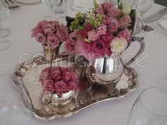 Pink floral arrangements of Roses displayed beautifully in our range of Silverware and Silver tea pots.