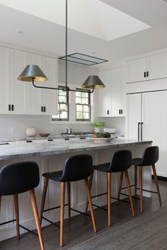 A bronze-and-brass, double-arm pendant from The Urban Electric Co. is suspended above the island, where four bar stools from Design Within Reach provide an easy setup for meals on the go | archdigest.com