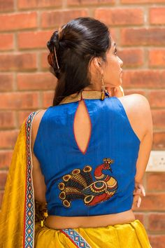 A cool high neck deep sleeveless blouse in blue raw silk with amazing details worked in in the form of a kalamkari back appliqué and a subtle goldish collar. You can so have fun pairing this number. A blue saree, a maroon saree, a white saree with blue details. Go ahead…pair away! #kalamkari #saree #india #blouse #houseofblouse