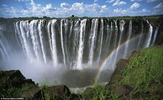 A rainbow forms as the turbulent waters of Zambezi River rush over Victoria Falls