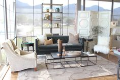 alice lane home collection | white screen, gold and white mongolian fur chair, nesting coffee table, marlena chair, gray velvet tufted sofa, bookcase