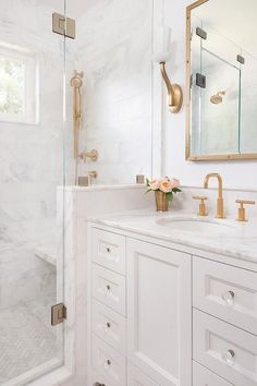 White and gold bathroom features a white washstand adorned with glass knobs topped with white marble fitted with an oval white porcelain sink and a brass Kohler faucet placed under a Restoration Hardware Brass RIvet Medicine Cabinet illuminated by brass up-light sconces.