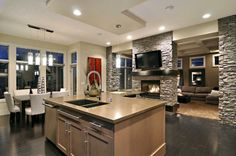 contemporary kitchen with a wood island and stacked stone accent wall. stone fireplace and flat screen tv. white dining table and chairs