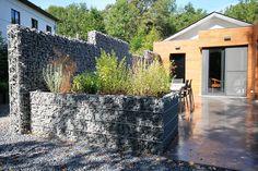 Designer Hochbeet aus Natursteinen mit Gabionen.